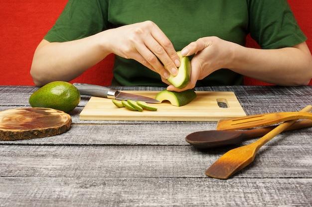 Processo de preparação de alimentos saudáveis. menina com uma camiseta verde descasca um abacate em uma mesa de madeira contra uma parede vermelha.
