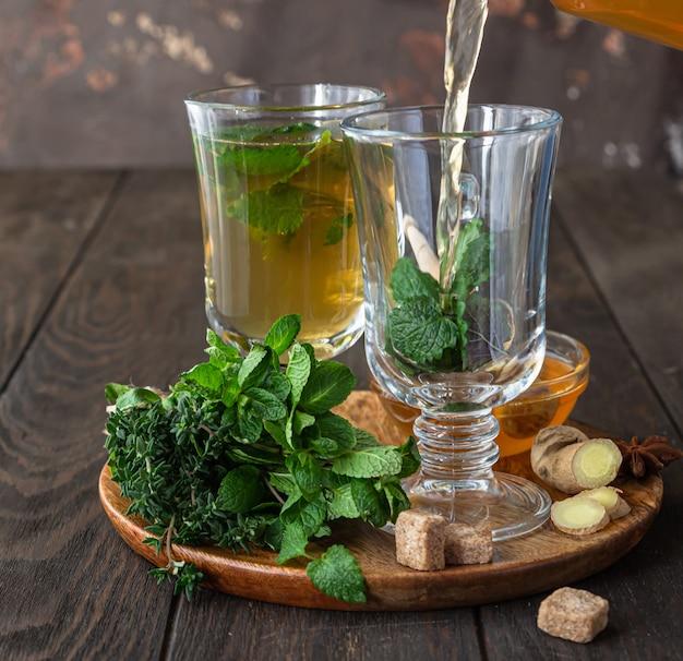 Processo de preparação de chá. chá quente de ervas ou de menta com ervas, gengibre e mel, fundo de madeira.