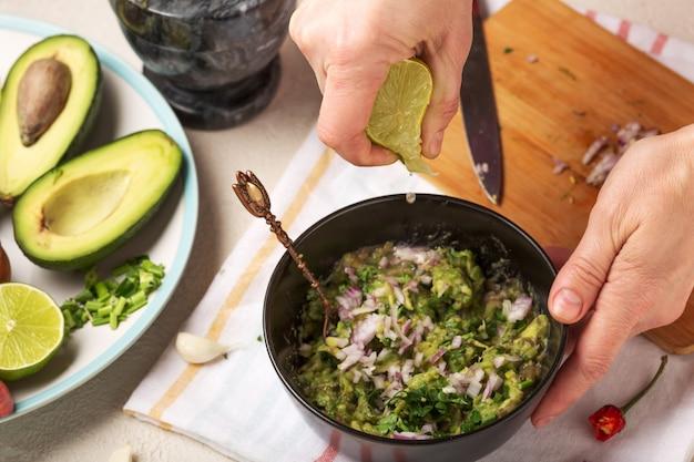 Processo de preparação de um guacamole de molho mexicano. mulher espremer suco de fruta limão.