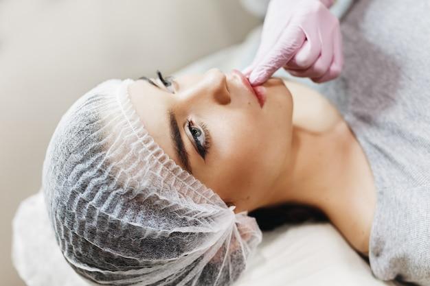 Processo de preparação para o aprimoramento labial. o médico retira ácido hialurônico na frente do paciente. a jovem com um rosto bonito no chapéu especial e mãos do médico na luva rosa