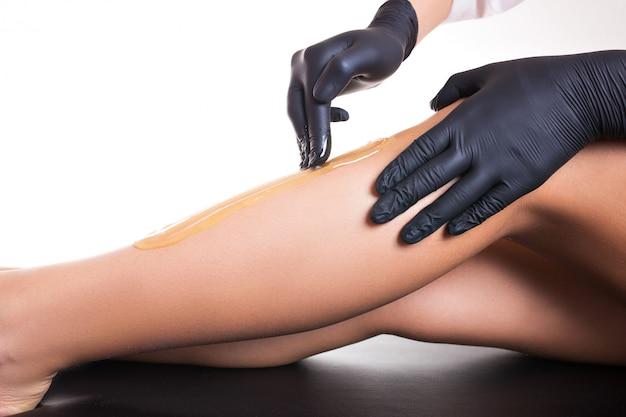 Processo de remoção de pêlos na perna feminina com depilação