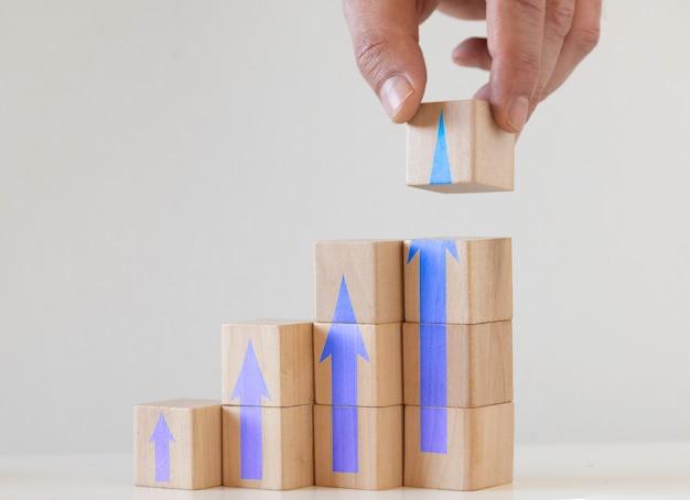 Processo de sucesso de crescimento de conceito de negócio. bloco de madeira empilhamento como escada de degraus com seta para cima.