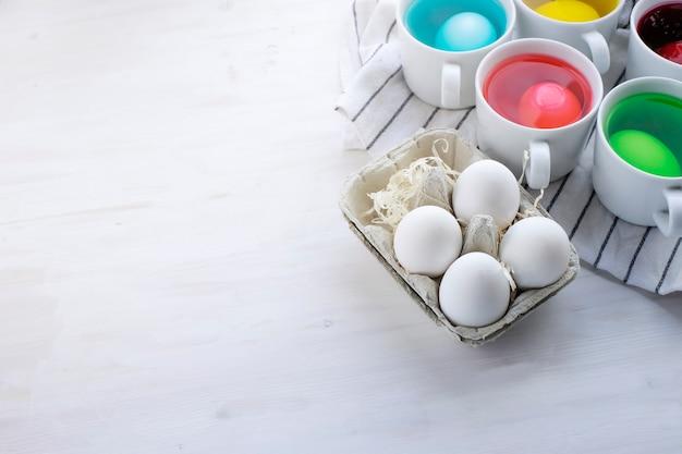 Processo de tingimento de ovos de páscoa e ovos em caixa sobre fundo de madeira clara