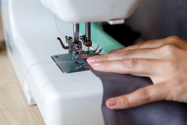 Processo de trabalho. costureira costurando tecido na máquina de costura