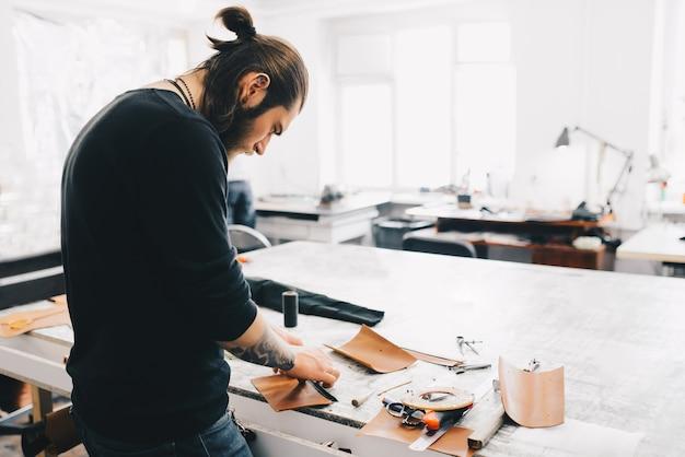 Processo de trabalho da bolsa de couro na oficina de couro.