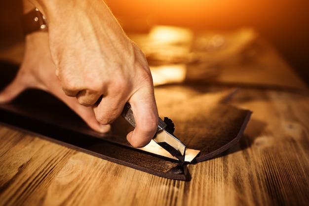 Processo de trabalho do cinto de couro na oficina de couro. ferramenta de exploração do homem. curtidor em curtume antigo. superfície da mesa de madeira. feche o braço do homem. luz quente para texto e design. tamanho do banner da web