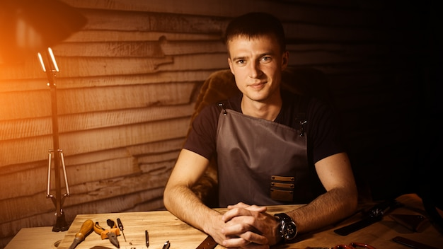 Processo de trabalho do cinto de couro na oficina de couro. homem de mãos dadas na mesa de madeira.