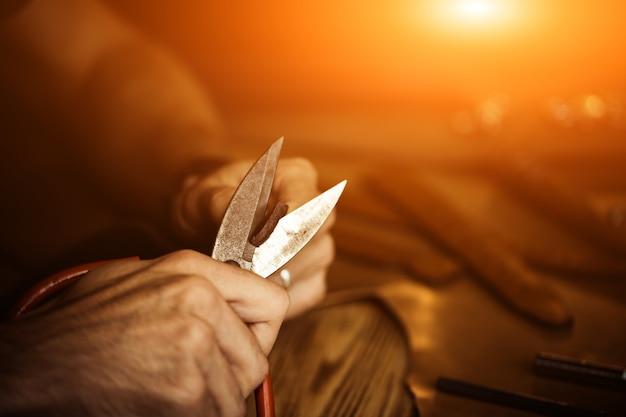 Processo de trabalho do cinto de couro na oficina de couro. homem segurando a ferramenta de elaboração e trabalho. curtidor em curtume antigo. superfície da mesa de madeira. feche o braço do homem. luz quente para texto e design