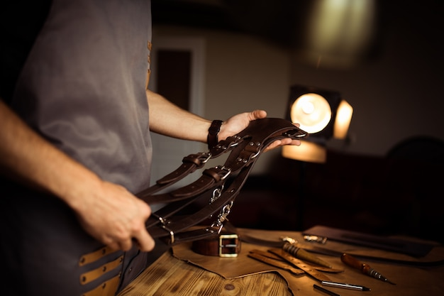 Processo de trabalho do cinto de couro na oficina de couro. homem segurando o cinto do fotógrafo para a câmera. ferramenta em fundo de madeira. curtidor em curtume antigo. feche o braço do mestre