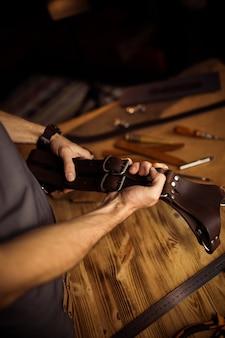 Processo de trabalho do cinto de couro na oficina de couro. homem segurando o cinto do fotógrafo para a câmera. ferramenta em fundo de madeira. curtidor em curtume antigo.