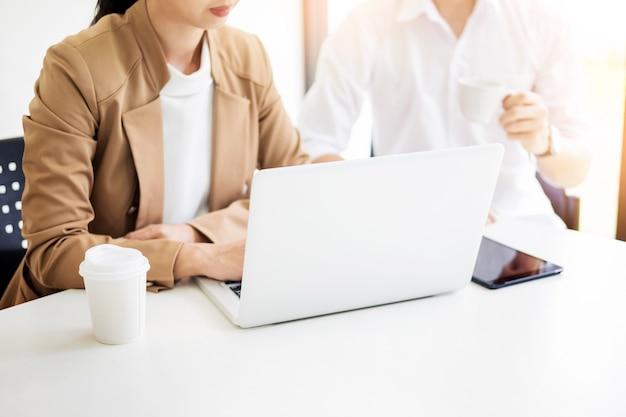 Processo de trabalho em equipe. equipe de jovens gerentes de negócios trabalhando com um novo projeto de inicialização. labtop na mesa de madeira, digitando teclado, mensagem de texto, analise os planos do gráfico.