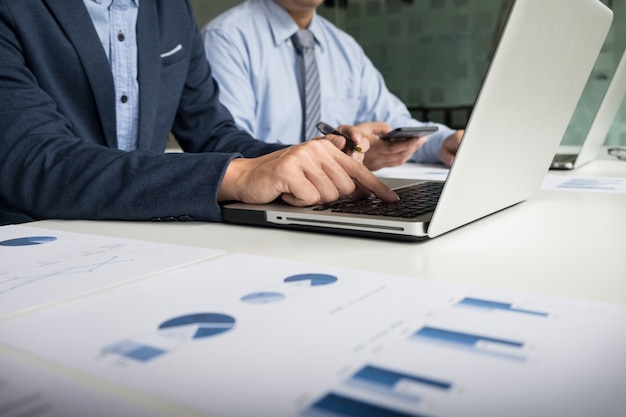 Processo de trabalho em equipe. equipe de jovens gerentes de negócios trabalhando com um novo projeto de inicialização. labtop na mesa de madeira, teclado de digitação, mensagem de texto, analise planos de gráficos.