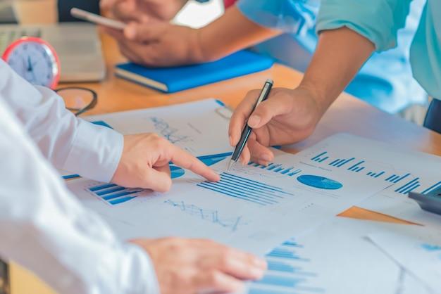 Processo de trabalho em equipe. equipe de jovens gerentes de negócios trabalhando com um novo projeto de inicialização. tabuleiro em mesa de madeira, teclado de digitação, mensagem de texto, analise planos de gráfico