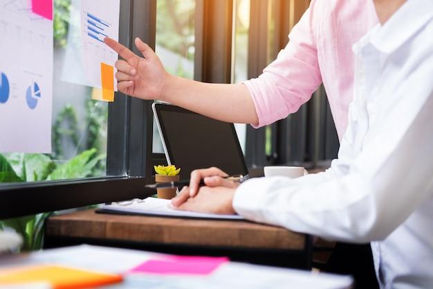 Processo de trabalho em equipe. jovens gerentes de negócios que trabalham com o projeto de inicialização. analise o plano do gráfico e a apresentação.