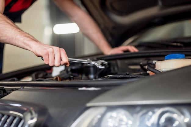 Processo de trabalho. mão masculina forte e experiente com uma chave inglesa no capô aberto do carro fazendo reparos