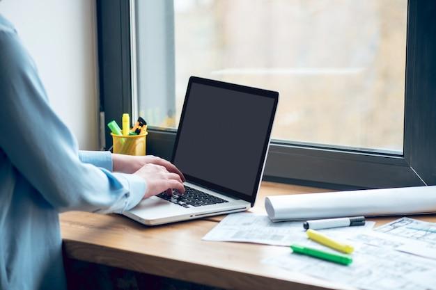 Processo de trabalho. mãos da mulher com uma blusa azul clara perto do teclado do laptop no parapeito da janela dentro de casa durante o dia, o rosto não está visível