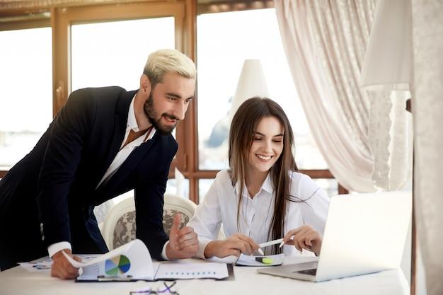 Processo de trabalho no centro de negócios de uma jovem morena e um homem atraente dentro do edifício, olhando para o laptop