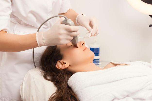 Processo do procedimento de limpeza por ultrassom da pele do rosto.
