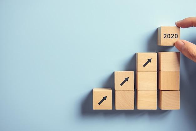 Processo do sucesso do crescimento 2020 do conceito do negócio, fim acima da mão da mulher que arranja o bloco de madeira que empilha como a escada da etapa no fundo azul de papel, espaço da cópia.