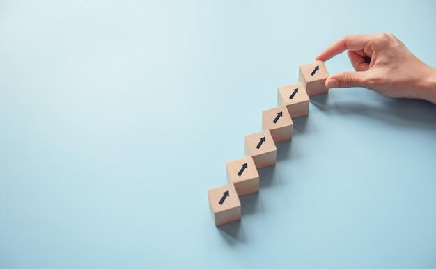 Processo do sucesso do crescimento do conceito do negócio, fim acima da mão da mulher que arranja o bloco de madeira que empilha como a escada da etapa no fundo azul de papel, espaço da cópia.