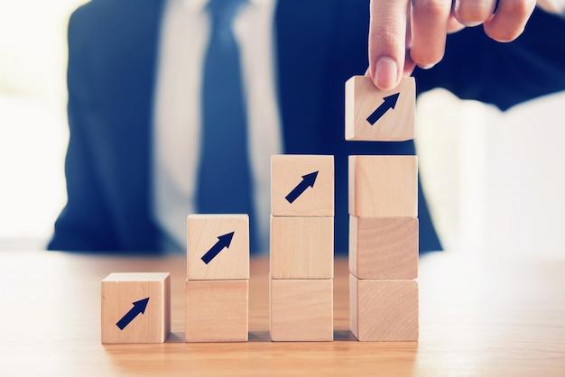 Processo do sucesso do crescimento do conceito do negócio, fim acima da mão do homem de negócios que arranja o cubo de madeira com a seta que empilha como a escada da etapa.