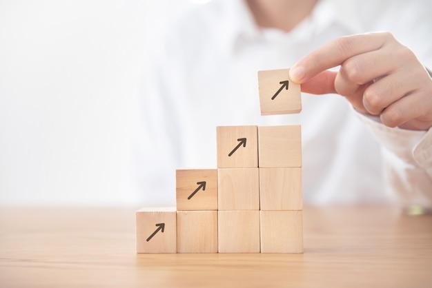 Processo do sucesso do crescimento do conceito do negócio, mão da mulher de negócios que arranja o cubo de madeira que empilha como a escada da etapa com a seta acima do símbolo.