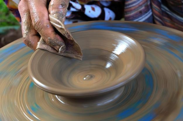 Processo tradicional de fazer louça de barro fresco molhado na roda de oleiro.