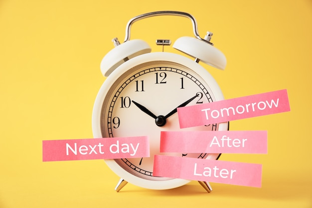 Procrastinação, atrasar e adiar o conceito. despertador com post-its mais tarde, amanhã, no dia seguinte e depois