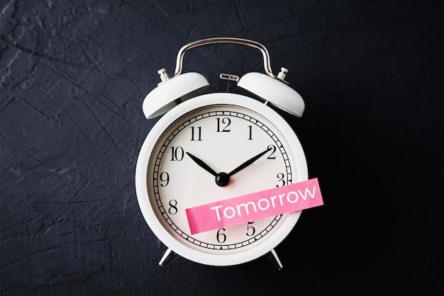 Procrastinação, atrasar e adiar o conceito. nota adesiva com a palavra amanhã no despertador branco