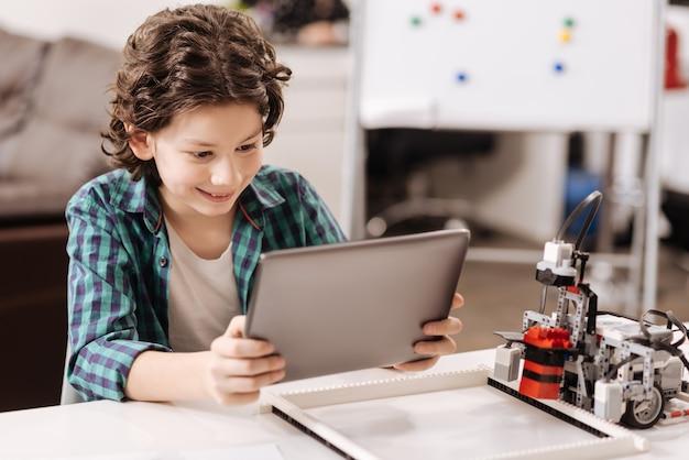 Procurando por invenções futurísticas. menino inteligente divertido e feliz sentado na sala de aula e usando um dispositivo digital enquanto estuda e expressa alegria