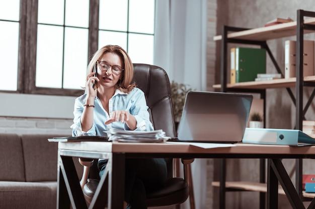 Procurando relatório. apelando de advogado de sucesso sentado em frente ao laptop e procurando um relatório importante
