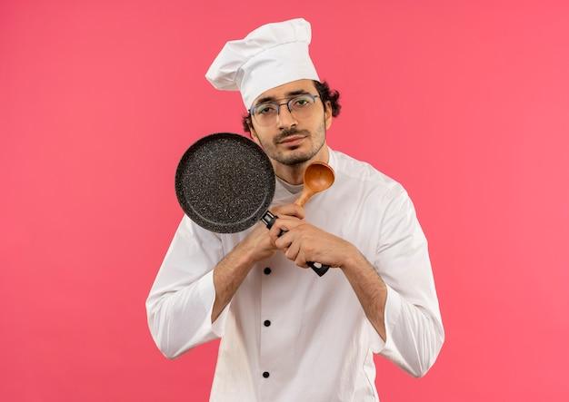 Procurando um jovem cozinheiro usando uniforme de chef e óculos, segurando e cruzando a frigideira com a colher