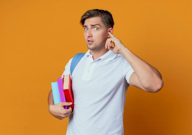 Procurando um jovem estudante bonito usando uma bolsa de costas segurando livros e fechando a orelha com o dedo