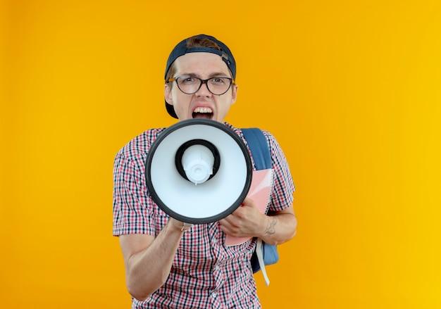 Procurando um jovem estudante vestindo uma bolsa, óculos e boné, fala no alto-falante segurando um caderno