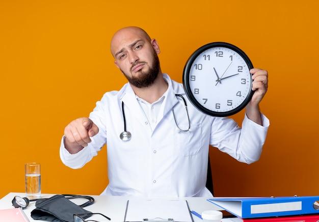 Procurando um jovem médico careca usando roupão médico e estetoscópio sentado na mesa de trabalho