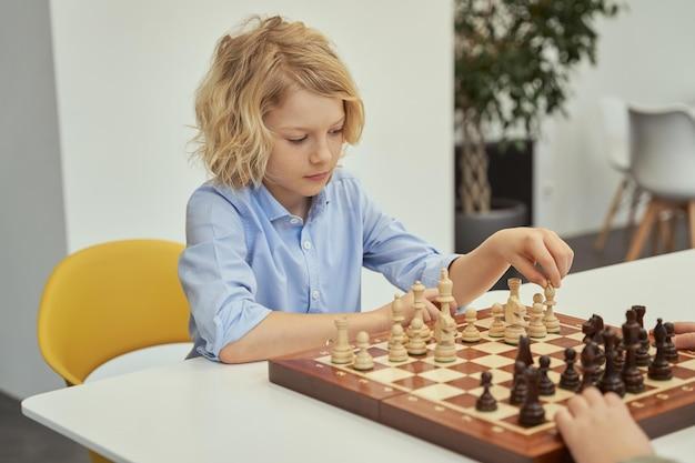 Procurando uma boa jogada, menino curioso, caucasiano, de camisa azul, sentado na sala de aula e