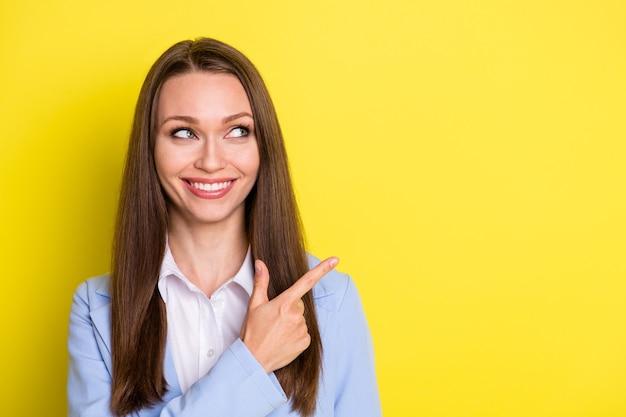 Procure anúncio de negócios. agente representativo positivo menina apontar dedo indicador copyspace demonstrar terno promocional isolado sobre fundo de cor de brilho brilhante