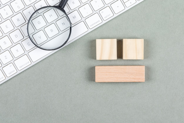 Procure o conceito com lupa, blocos de madeira, teclado na vista superior do plano de fundo cinza. imagem horizontal