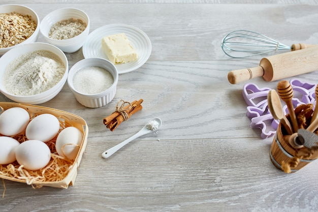 Produção caseira de biscoitos frescos saudáveis com ingredientes naturais em um fundo cinza claro