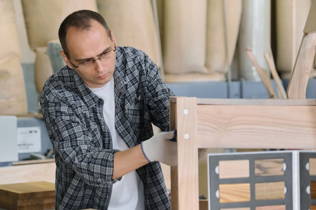 Produção da mobília, carpinteiro masculino do retrato na oficina de madeira que faz a cadeira de madeira.