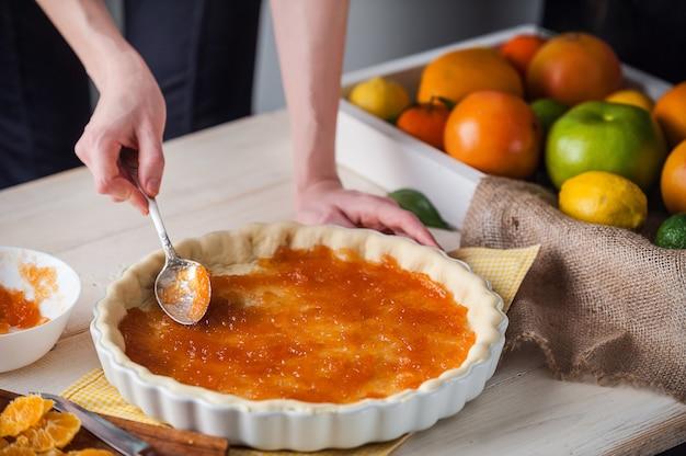 Produção de bolo com marmelada cítrica e fatias de tangerina