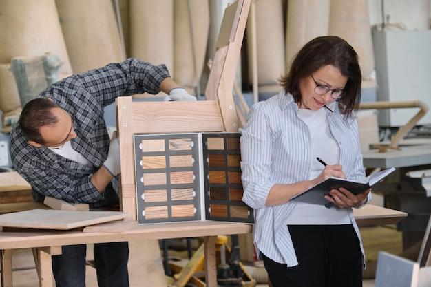Produção de marcenaria de móveis, marceneiro masculino e designer feminino
