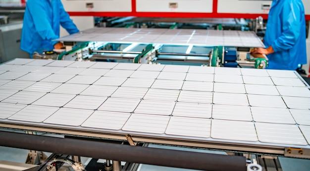 Produção de painéis solares, homens que trabalham em fábrica. closeup de máquinas pesadas na fábrica de painéis de produção solar.