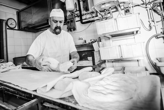 Produção de pão assado com forno de lenha em padaria