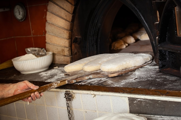 Produção de pão assado com forno de lenha em uma padaria.