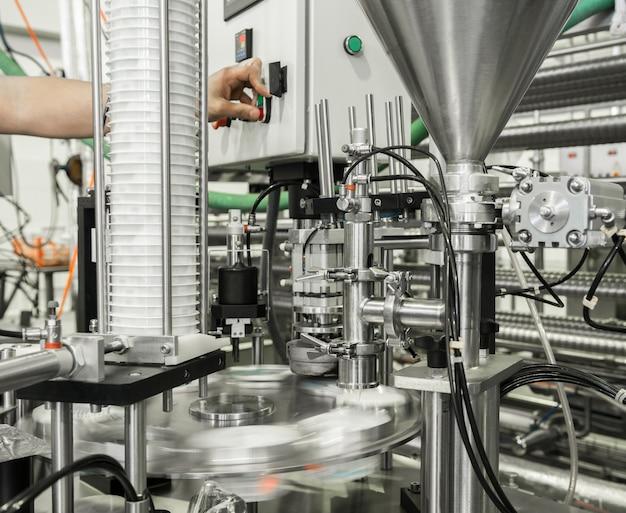 Produção e envase de iogurte em copos plásticos. equipamento na fábrica de laticínios