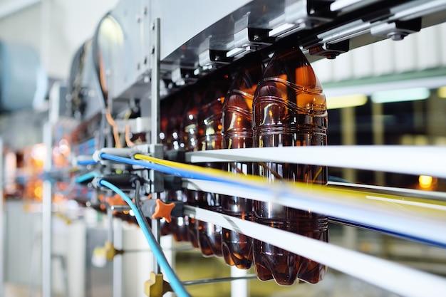 Produção industrial de garrafas plásticas para bebidas com baixo teor de álcool, refrigerante e óleo de girassol. garrafas pet vazias de cor marrom no fundo de equipamentos modernos.