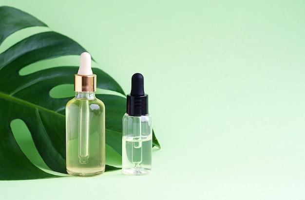Produto cosmético à base de plantas naturais para o cuidado da pele. soro e óleo em frascos de vidro com folha de monstro