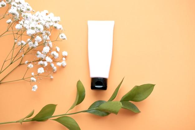 Produto cosmético de beleza, com folhas verdes e flores brancas de gypsophila. o conceito de dia-mãe das mulheres. vista plana leiga, superior.