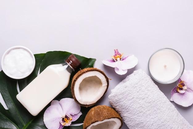 Produto cosmético de coco, folhas e flores tropicais. conceito de spa natural.